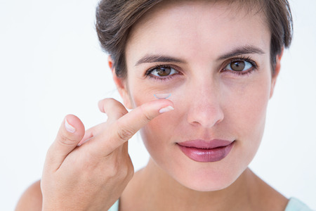 contact lens: Pretty woman applying contact lens on white background Stock Photo