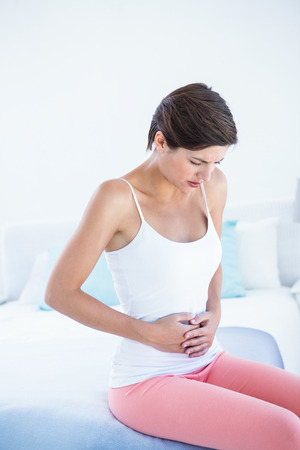 ill abdomen: Beautiful woman with stomach pain at home in the bedroom