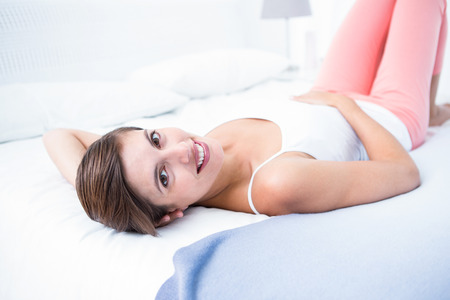 Happy woman smiling at camera at home in the bedroom photo