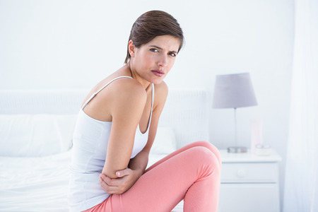 young  brunette: Beautiful brunette suffering from stomach pain at home in the bedroom Stock Photo