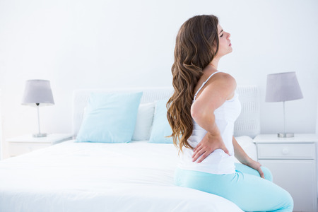 in the back: Attractive woman with back pain at home in the bedroom