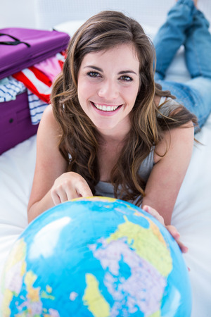 Beautiful woman with a suitcase pointing on a globe at home in the bedroom photo