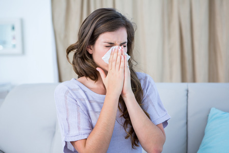 human nose: Sick woman blowing her nose at home in the living room Stock Photo