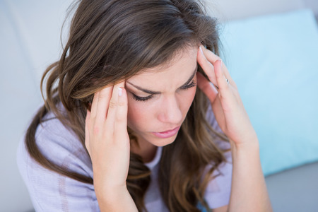 pounding head: Sick woman suffering from head ache at home in the living room Stock Photo