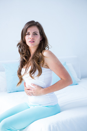 Attractive woman with stomach pain at home in the bedroom