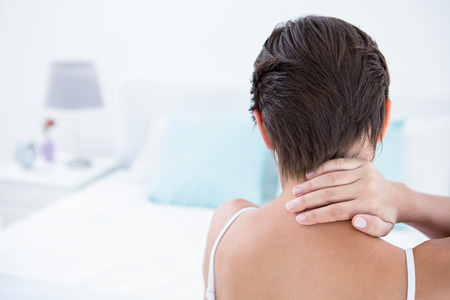 hait: Woman suffering from neck pain at home in the bedroom
