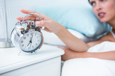 extending: Sleepy young woman in bed extending hand to alarm clock at home in the bedroom