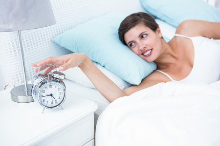 extending: Happy woman extending hand to alarm clock at home in the bedroom