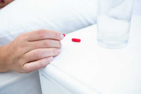sleeping pills: Woman taking pills before sleeping at home in the bedroom