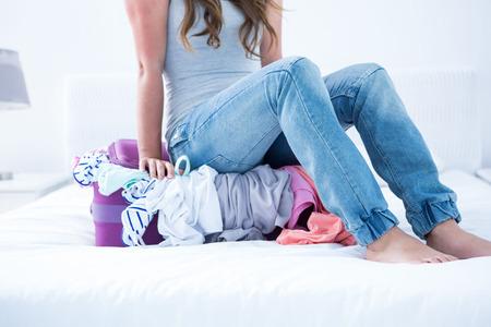 mujer con maleta: Mujer sentada en su maleta en casa en el dormitorio