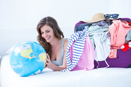 Smiling brunette lying on bed looking her globe at home in the bedroom photo