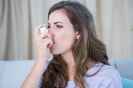 asma: Mujer bonita que toma su inhalador en casa en la sala de estar Foto de archivo