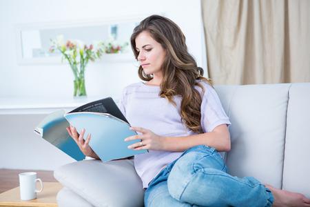 거실에서 집에서 잡지를 읽고 평화로운 여자 스톡 콘텐츠