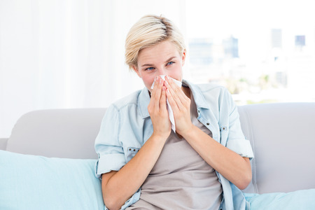 Sick blonde woman blowing her nose in the living room photo