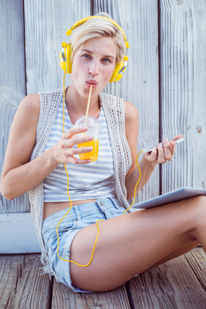 Pretty blonde woman listening music with her mobile phone and drinking orange juice on wooden background photo