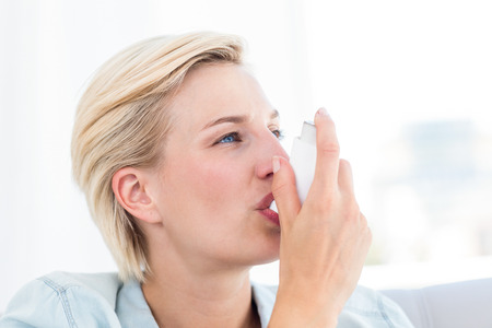 inhaler: Pretty blonde woman using her inhaler in the living room Stock Photo