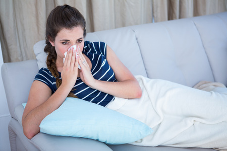 Sick woman blowing her nose on couch at home in the living room photo