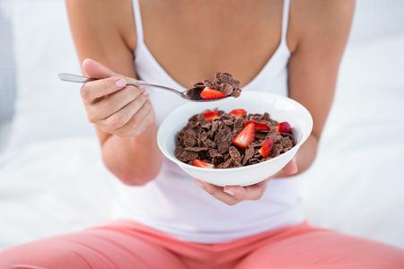 comiendo cereal: Mujer atractiva que come el cereal en su cama en su casa en el dormitorio
