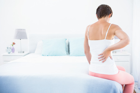 hand pain: Woman with back pain at home in the bedroom