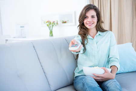 changing channel: Happy brunette watching television with bowl of popcorn at home in the living room Stock Photo