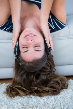 Pretty brunette listening music on couch in the living room photo