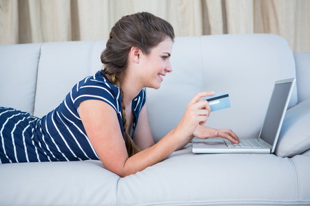 online purchase: Pretty woman lying on couch doing online shopping at home in the living room Stock Photo