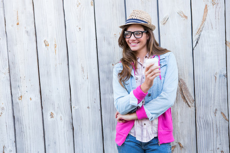 disposable cup: Cute woman holding disposable cup coffee against wooden planks