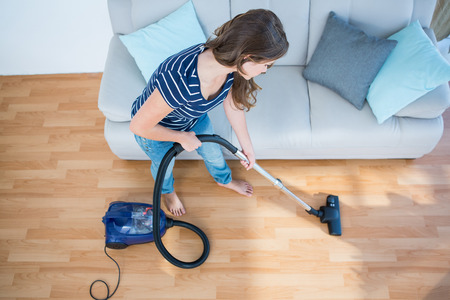 young  brunette: Woman using vacuum cleaner on wooden floor at home in the living room