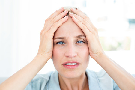 Blonde woman having headache in the living room Stock Photo