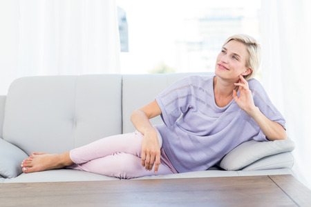 sitting room: Pretty blonde woman relaxing on the couch in the living room Stock Photo