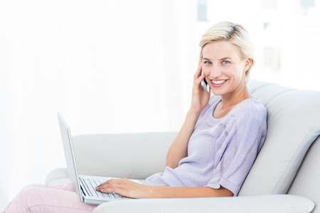 Pretty blonde woman calling on the phone and using her laptop in the living room photo