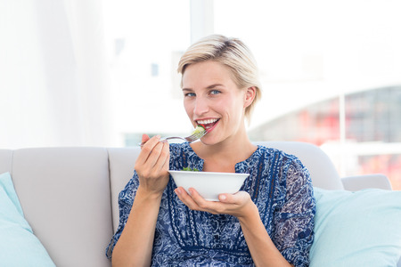 fair woman: Pretty blonde woman eating bowl of salad in the living room Stock Photo