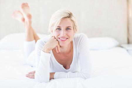 Sorridente donna bionda sdraiata sul letto nella sua camera da letto