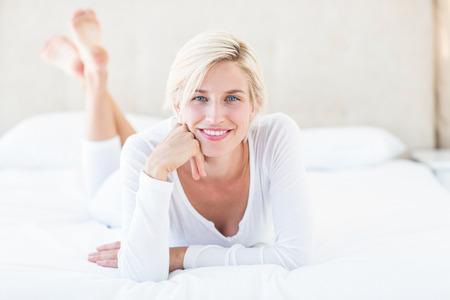 Smiling blonde woman lying on the bed in her bedroom Archivio Fotografico