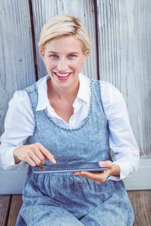 fair woman: Pretty blonde woman using her tablet on wooden background