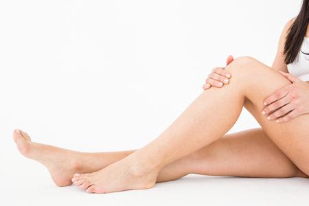 dolor rodilla: Mujer natural con dolor de rodilla en el fondo blanco Foto de archivo
