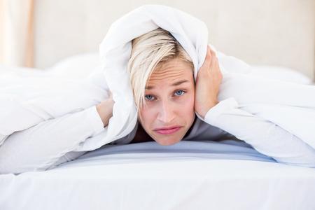 desolaci�n: Malestar mujer rubia acostado en la cama en su dormitorio Foto de archivo