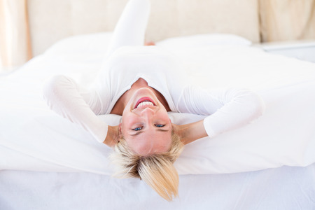 Smiling blonde woman lying on the bed in her bedroom photo