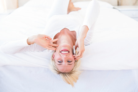 Smiling blonde woman lying on the bed and calling on the phone in her bedroom photo