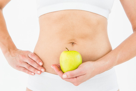 body concern: Fit woman holding an apple in front of her belly on white background