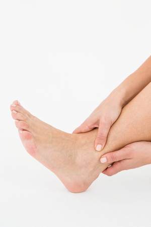 achilles tendon: Woman touching her painful ankle on white background Stock Photo