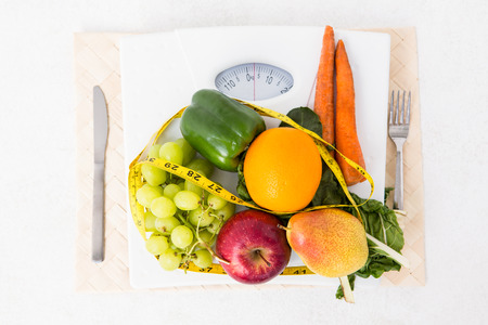 weighing scales: Bilance con frutta e verdure su sfondo bianco