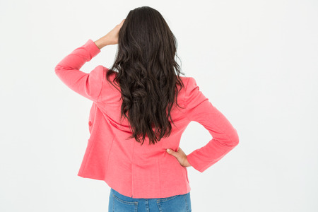 looking away from camera: Elegant brunette standing back to camera and looking away on white background