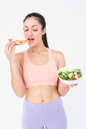 dudando: Pretty brunette eating pizza and holding salad on white background Foto de archivo