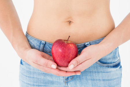 body concern: Fit woman standing with red apple on white background