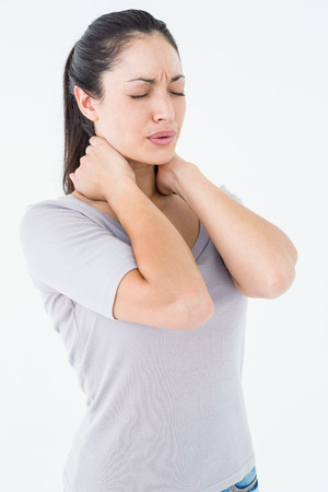wincing: Brunette suffering from neck pain on white ackground