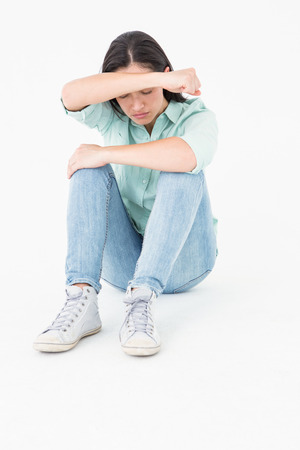 Sad woman sitting on the floor and hiding her face on white backgroung Stock Photo