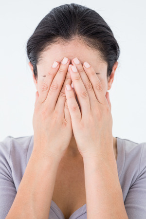 wistfulness: Sad woman hiding her face on white background Stock Photo