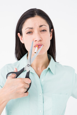 fag: Brunette cutting cigarette with scissors on white background Stock Photo