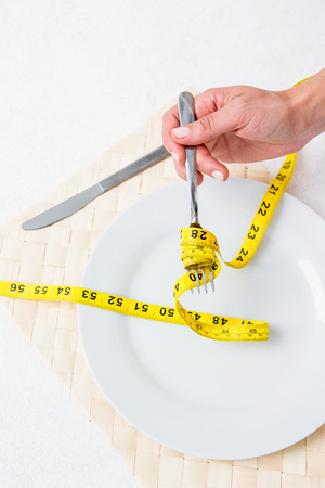 Measuring tape around the fork on white background photo